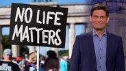 """Ehring neben einem Schild mit der Aufschrift """"No Life matters""""."""
