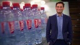 Ehring vor Plastik-Wasserflaschen von Vittel