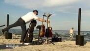 Ein Musiker baut an einem Strand seine Instrumente auf.