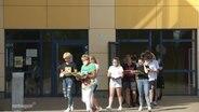 Schüler und Lehrer verlassen mit ihren Lernutensilien und Masken tragend ihr Schulgebäude.