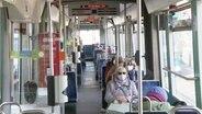 Innenaufnahme einer Straßenbahn - alle Fahrgäste tragen eine Maske.