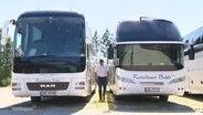 Zwei Reisebusse und in der Mitte ein Mann.