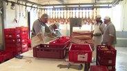 Mitarbeiter einer Schlachterei an der Arbeit, beim Zerteilen.
