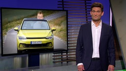 Christian Ehring und im Hintergrund ein Mann in einem kleinen Auto.