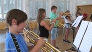 Mehrere Kinder beim Unterricht von Blasinstrumenten.