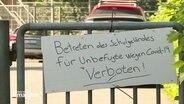 """Ein Schild mit der Aufschrift """"Betreten des Schulgeländes für Unbefugte wegen Covid-19 Verboten!"""" hängt an einem Schultor."""