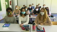 Eine Schulklasse sitzt mit Masken im Unterricht