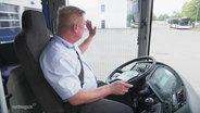 Busfahrer Heiko Müller winkt aus dem Fenster