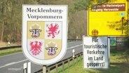 Ein Straßenschild zeigt das Wappen von Mecklenburg-Vorpommern, daneben steht auf einem anderen Schild: für touristische Verkehre im Land gesperrt!