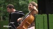 Eine lächelnde Cellistin und ein Akkordeonspieler musizieren.