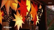Beleuchtete Sterne aus Papier an einem Weihnachtsmarktstand.