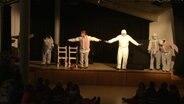 Theaterschauspieler mit Maske und Schutzanzug auf der Bühne.