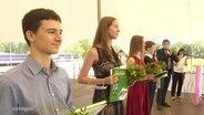 Jugendliche auf einer Jugendweihfeier mit Blumen und Geschenken.