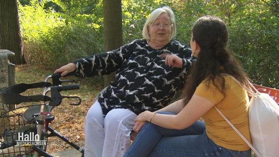 Gudrun Klie (left) is sitting on a park bench with Svenja Dehler and is talking.