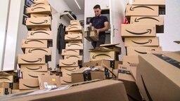 Ein junger Mann sitzt inmitten von Amazon-Paketen.
