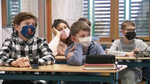 Étudiant avec masque dans une salle de classe.