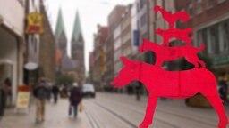 Ein Piktogramm der Bremer Stadtmusikanten auf dem Gehsteig.