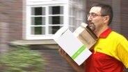 Autor Reinhard Schädler mit Paketen auf dem Arm