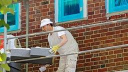 Die passgenau zugeschnittenen Dämmplatten werden auf der Rückseite mit ausreichend Kleber bestrichen, damit sie fest auf der Wand haften. © © NDR/Güven Purtul, honorarfrei