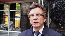 Prof. Reinhard Ries, Branddirektor Frankfurt vor einer verkohlten Fassade. © NDR