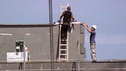 Bauarbeiter bringen Styropor-Blöcke zur Wärmedämmung an einer Fassade an. © NDR