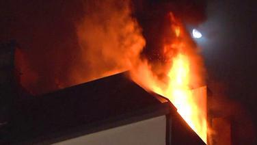 Nachtaufnahme. Flammen über dem Dachstuhl eines Mietshauses. © NDR