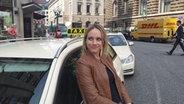 NDR Reporterin Stefanie Gromes lehnt sich an ein Taxi. © NDR / Fabienne Hurst