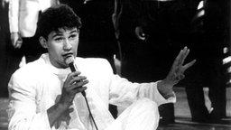 """Der irische Sänger Johnny Logan sitzt nach seinem Sieg beim 32. Grand Prix am 9. Mai 1987  in Brüssel im Schneidersitz auf der Bühne und singt für die Zuschauer noch einmal seinen Siegertitel """"Hold me now"""". © picture-alliance / dpa Foto: epa Lehtikuva"""