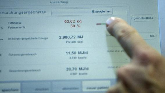 Finger zeigt auf Bildschirm mit Ergebnissen einer Bioimpedanzmessung. © NDR Foto: nonfictionplanet