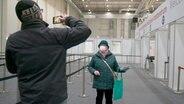 Gerda F. (80) aus Lohbrügge wird von ihrem Sohn vor dem Impfzentrum fotografiert. © NDR
