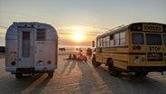 Der Schulbus-Camper und ein klassischer, silberner US-Camper stehen an einem Strand. Die Sonne geht unter. © NDR