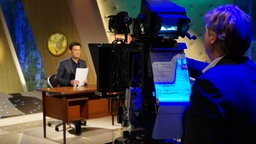 Christian Ehring sitzt am Schreibtisch im extra 3 Studio, eine Kamera filmt ihn. © NDR Foto: Andreas Lange