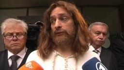 Jesus vor dem Gerichtsgebäude, er verklagt die CSU.