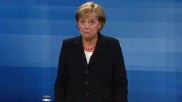 Angela Merkel guckt verdutzt in die Kamera.