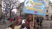 """Tobias Schlegl mit langem Bart und Hippie-Klamotten hält ein Schild hoch mit der Aufschrift: """"Salafisten für den Weltfrieden""""."""