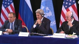 Sergej Lawrow sitzt neben John Kerry auf dem Podium.