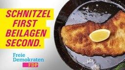 Ein FDP-Wahlplakat mit einem Schnitzel in der Pfanne und der Aufschrift: Schnitzel first, Beilagen second