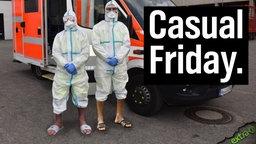 Casual Friday - Zwei Menschen in Ganzkörperschutzanzügen, an den Beinen hochgekrempelt mit Socken und Adiletten/Sandalen