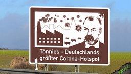 Autobahnschild mit der Aufschrift: Tönnies - Deutschlands größter Corona-Hotspot.