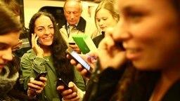 Eine Gruppe junger Menschen spielt oder telefoniert mit Smartphones.