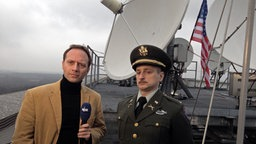Dennis Kaupp interviewt vor großen Sendeantennen den uniformierten Johannes Schlüter. © NDR Foto: Sven-Oliver Durke