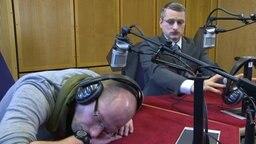 Ein Radiomoderator liegt eingeschlafen auf dem Tisch, Johannes Schlüter blickt ihn fragend an. © NDR Foto: Screenshot