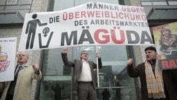 Johannes Schlüter steht protestierend unter einem Plakat mit der Aufschrift MÄGÜDA: Männer gegen die Überweiblichung des Arbeitsmarktes.