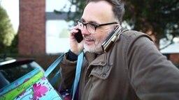 Ein Mann mit zwei Telefonen.