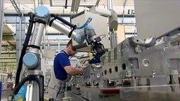 Das Bild zeigt einen Arbeiter, der neben einem Roboter Motor-Zylinderköpfe fertigt. © NDR