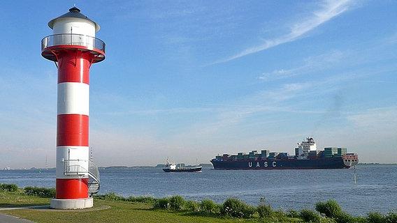 Elbe mit Leuchtturm und großem Containerschiff. © NDR Foto: Günther Metzinger, Jork