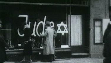 """Mit der Aufschrift """"Jude"""" und einem Judenstern versehenes Schaufenster, davor stehen Passanten"""