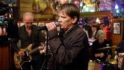 Der Sänger der Band Element of Crime steht vor einem Mikrofon und singt. © NDR/Morris Mac Matzen