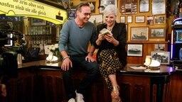Torsten Sträter sitzt neben Ina Müller auf der Theke, zusammen schauen sie sich Bierdeckel an. © NDR/Morris Mac Matzen