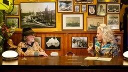 Helge Schneider und Ina Müller sitzen nebeneinander an einem Tresen und blicken sich an © NDR/Morris Mac Matzen Foto: Morris Mac Matzen